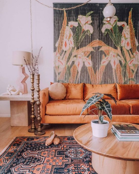 un soggiorno boho con un arazzo floreale, un divano arancione, un tavolo rotondo e un tavolino più portacandele e un tappeto boho
