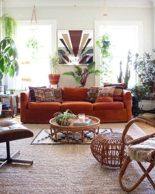 un soggiorno boho con un divano di velluto arancione come centrotavola, piante in vaso e mobili in rattan e pelle, tappeti boho