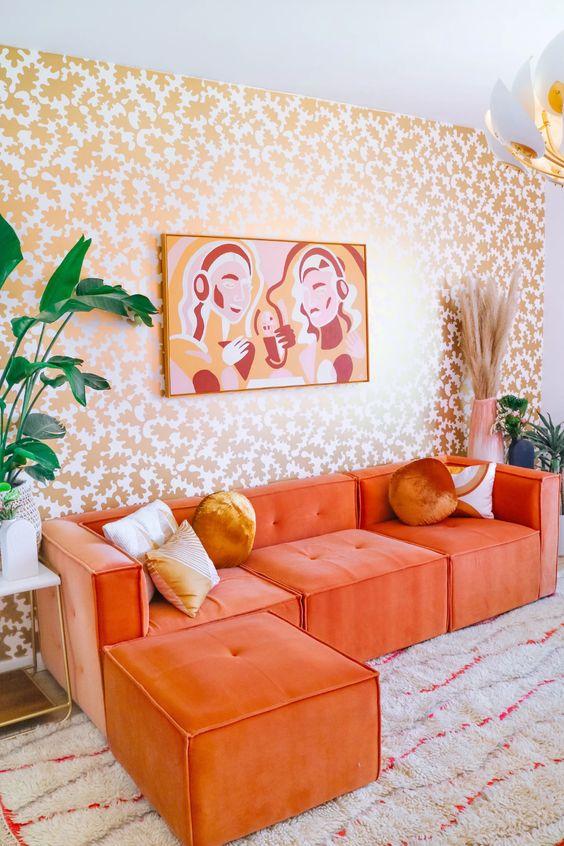 un audace soggiorno con una parete stampata botanica, un componibile arancione, un'opera d'arte audace e alcune piante e fiori