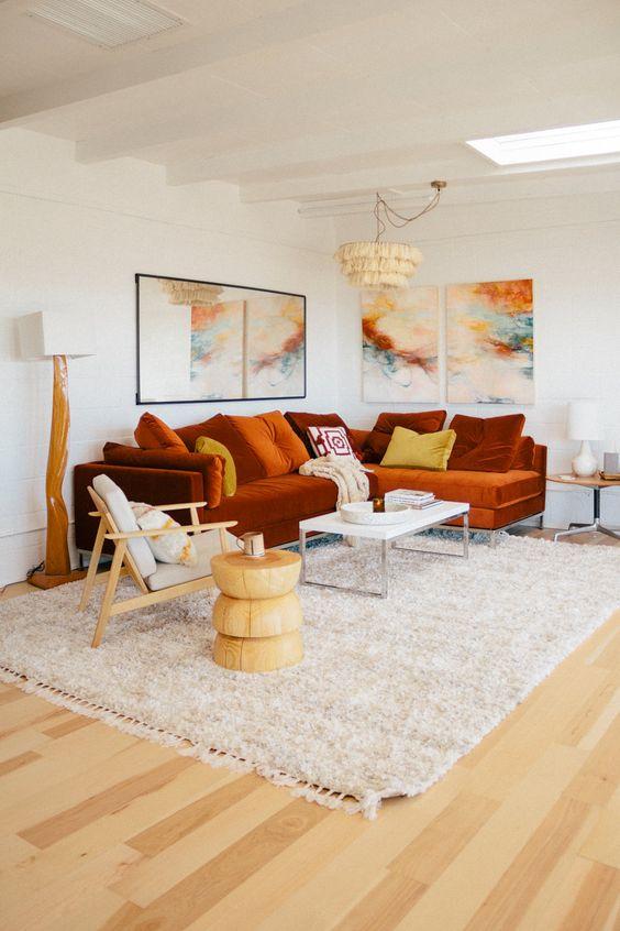 un audace soggiorno con un componibile color ruggine e una luminosa galleria a parete più lampade di tendenza