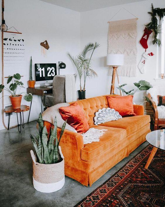 un soggiorno boho con un divano arancione, piante in vaso, un macramè appeso, un piccolo spazio di lavoro nell'angolo è fantastico