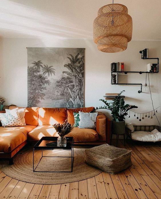 un soggiorno boho con un componibile arancione, un tavolo basso, un pouf in iuta e un tappeto, una lampada a sospensione intrecciata e piante in vaso