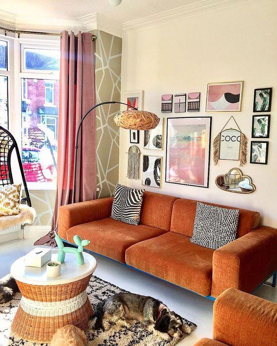 uno splendido soggiorno eclettico con un divano color ruggine e una sedia abbinata, un tavolo rotondo, una graziosa galleria a parete e una lampada da terra