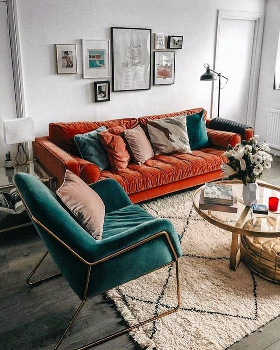 un incantevole soggiorno con un audace divano arancione bruciato, una sedia verde acqua e cuscini abbinati, oltre a una bella parete della galleria
