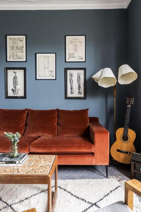 un soggiorno chic con pareti blu scuro, un divano color ruggine, una galleria a muro, una lampada da terra e un tavolo basso con piastrelle è wow