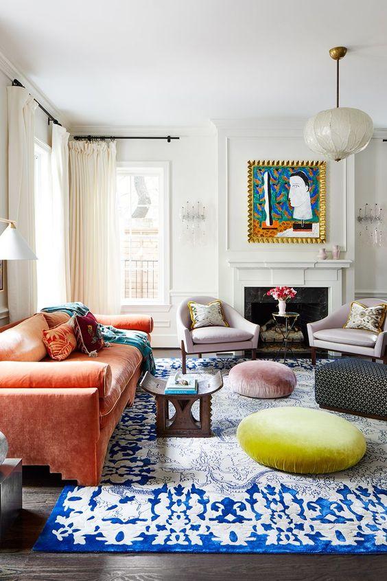 un colorato eclettico soggiorno con camino, sedie lilla, un divano arancione, mobili marocchini, un tappeto e pouf è audace