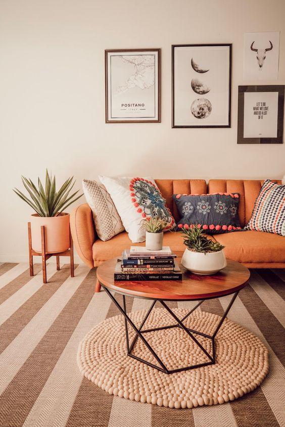 un delizioso soggiorno boho con un divano in pelle arancione, un tappeto di perline di legno e un tavolo geo, una parete della galleria monocromatica