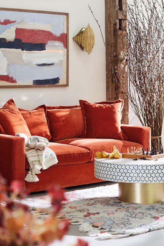un luminoso soggiorno con un divano arancione, un tavolo rotondo, un'opera d'arte audace e rami fioriti disposti per l'arredamento