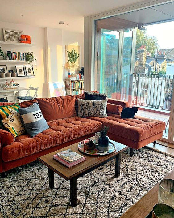 un bel soggiorno con un componibile color ruggine, un tavolo basso, mensole sospese e piante in vaso qua e là