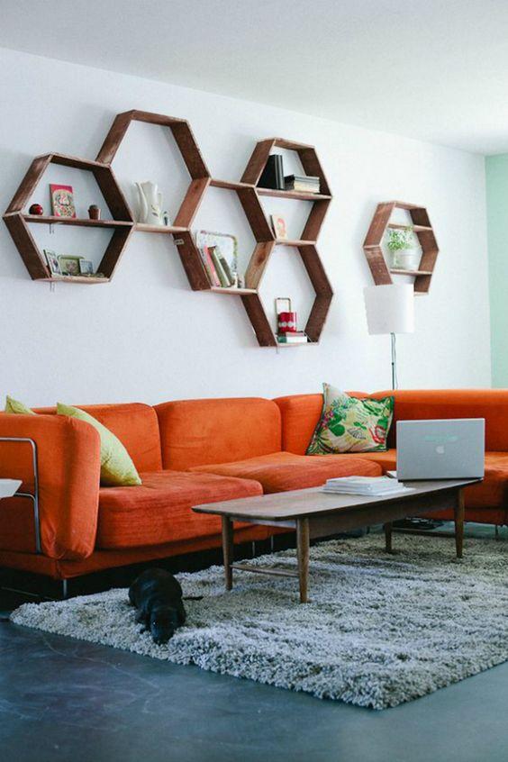 un soggiorno moderno della metà del secolo con un divano arancione, mensole esagonali, un tavolo basso e cuscini colorati è accogliente