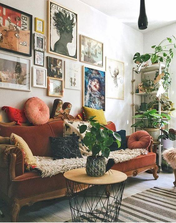 un soggiorno massimalista con una galleria colorata, un divano vintage color ruggine, un tavolo rotondo e piante in vaso