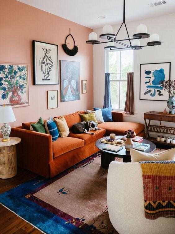 un soggiorno massimalista con un muro rosa accento, un divano arancione con cuscini colorati, mobili neutri e tessuti audaci più tende colorate