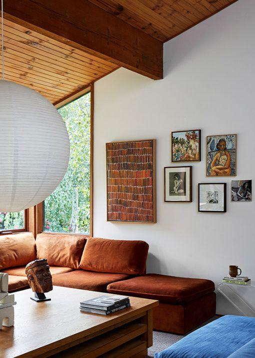 uno spazio moderno della metà del secolo con un grande componibile color ruggine, un tavolo basso in legno e un pouf blu più un bizzarro muro della galleria