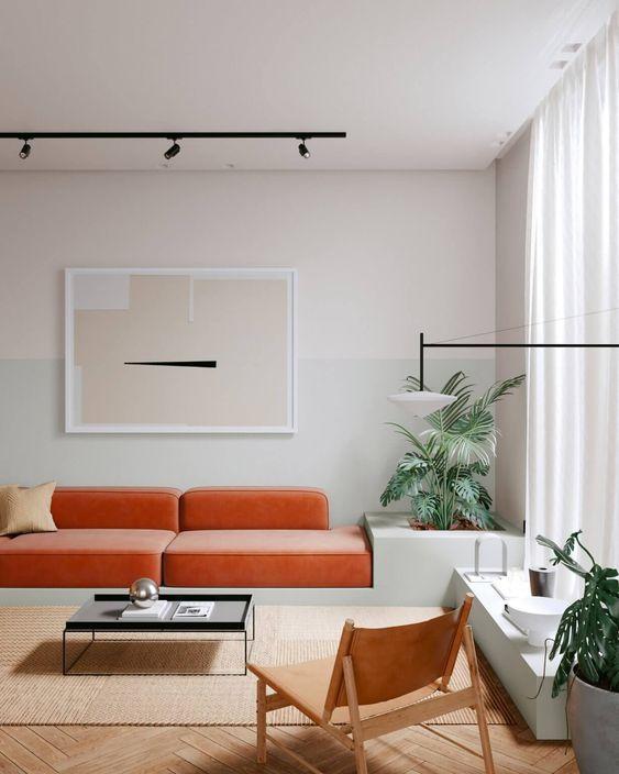 un soggiorno minimalista con un divano in velluto arancione, un tavolo basso e una sedia in pelle, piante in vaso e un'opera d'arte astratta