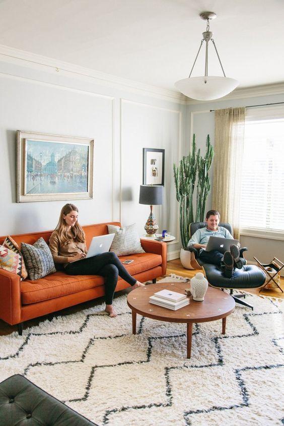 un soggiorno boho della metà del secolo realizzato in colori neutri, con un divano arancione e una sedia in pelle nera più un cactus e opere d'arte
