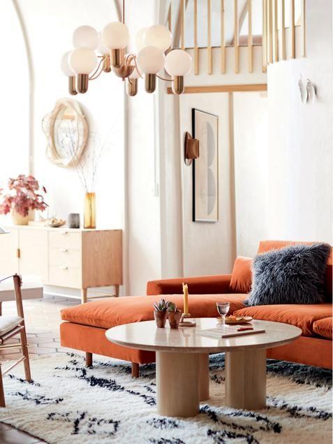 un soggiorno moderno realizzato in neutri, con un componibile color ruggine, un tavolo rotondo basso e un lampadario moderno della metà del secolo per illuminare lo spazio