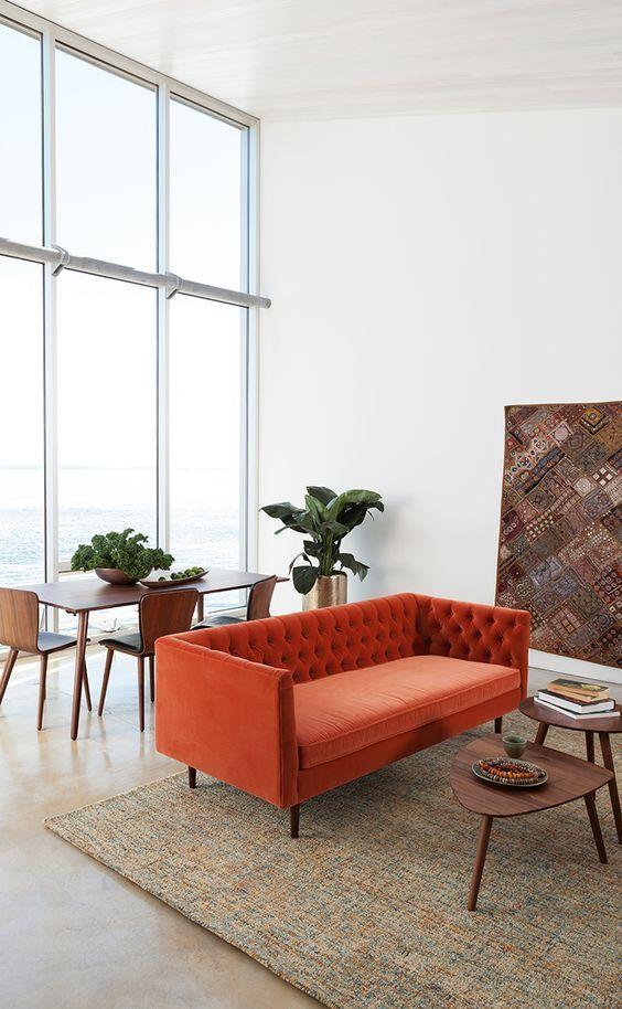 un soffitto neutro a doppia altezza, con un divano arancione, un duo di tavoli e una zona pranzo vicino alla finestra