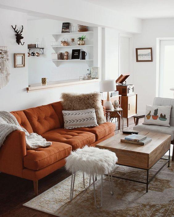 un soggiorno abbastanza neutro in stile boho, con un divano color ruggine, un tavolino basso e uno sgabello in pelliccia, i tessuti stampati sono molto accoglienti