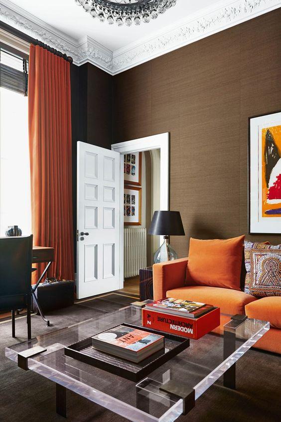 un soggiorno moderno con un divano arancione, un tavolo basso in acrilico, una scrivania e una sedia in pelle più un lampadario di cristallo