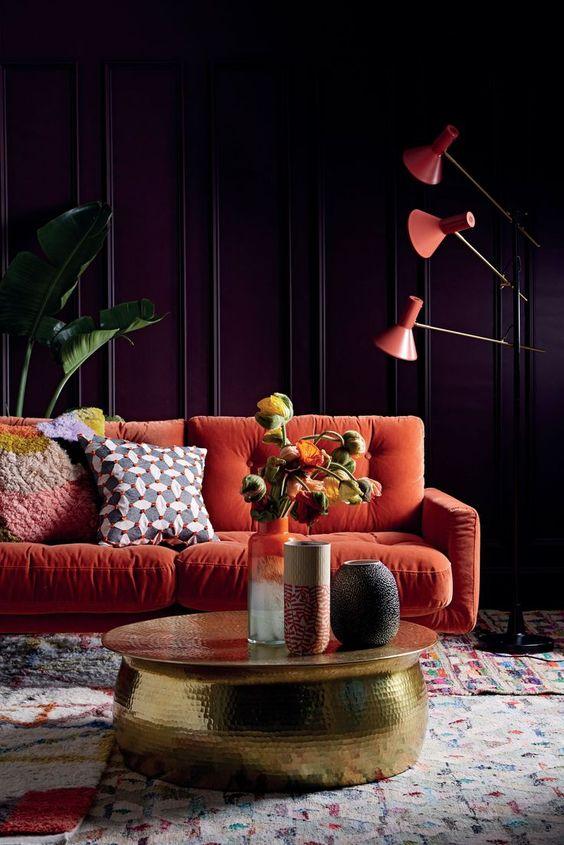 un soggiorno lunatico con pareti rivestite di pannelli viola, un divano arancione, lampade da terra arancioni, un tavolo martellato d'oro e piante importanti
