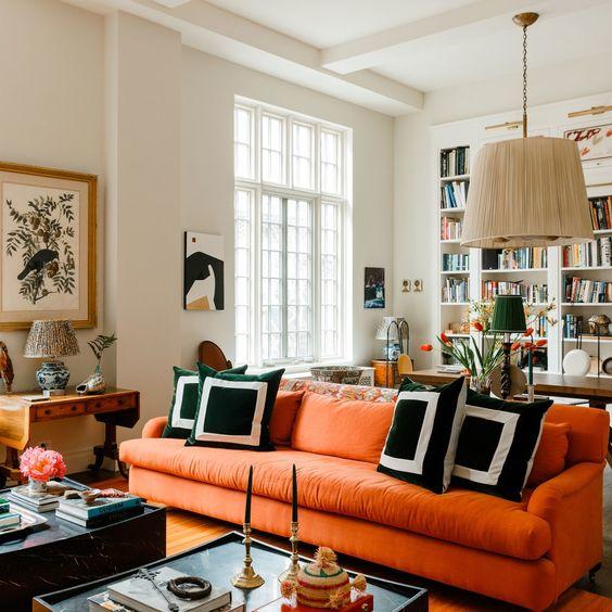 un soggiorno moderno con un divano arancione, una lampada a sospensione, cuscini grafici, alcuni tavolini da caffè e incantevoli opere d'arte