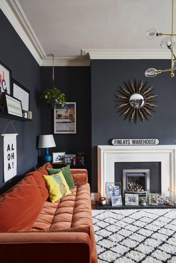 un soggiorno lunatico con un finto caminetto, opere d'arte, stampe e candele, un divano color ruggine e una graziosa galleria a parete