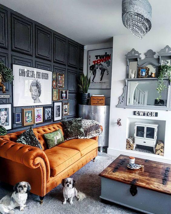 un eccentrico soggiorno con una parete rivestita di pannelli neri, un divano arancione, un mini focolare e uno specchio, una bizzarra galleria a muro e un tavolino basso