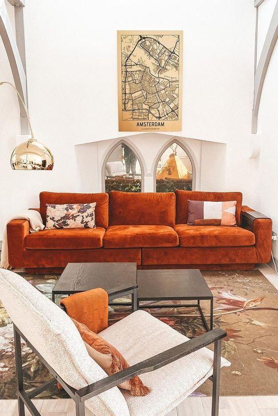 un soggiorno raffinato con un divano color ruggine, un duo di tavoli, una sedia color crema, una lampada da terra lucida è sorprendente