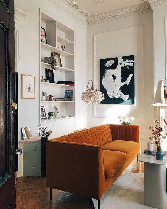 un raffinato soggiorno con una nicchia con scaffali incorporati, un divano color ruggine, un'opera d'arte in bianco e nero e fiori secchi