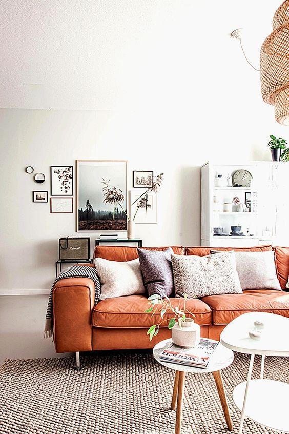 un sereno soggiorno scandinavo con mobili neutri, una galleria a muro chic e un divano in pelle arancione con cuscini boho è sorprendente