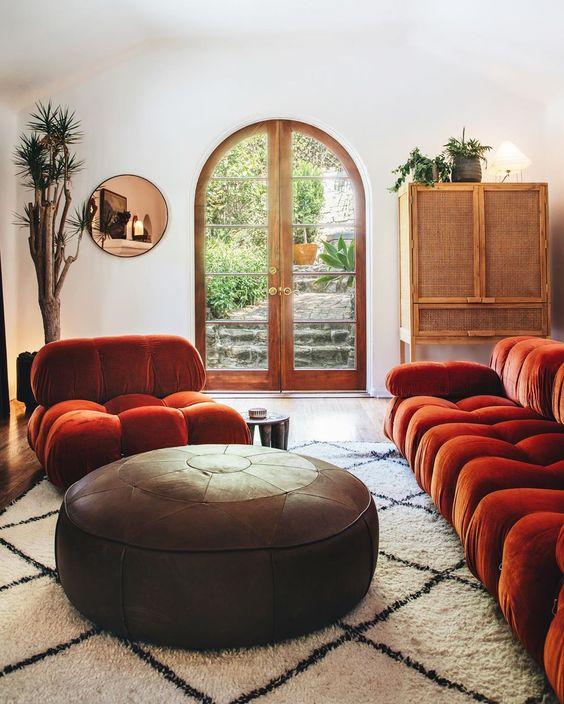un raffinato soggiorno in tonalità neutre, con un divano e una sedia arancione bruciato, un pouf rotondo in pelle, una credenza in rattan