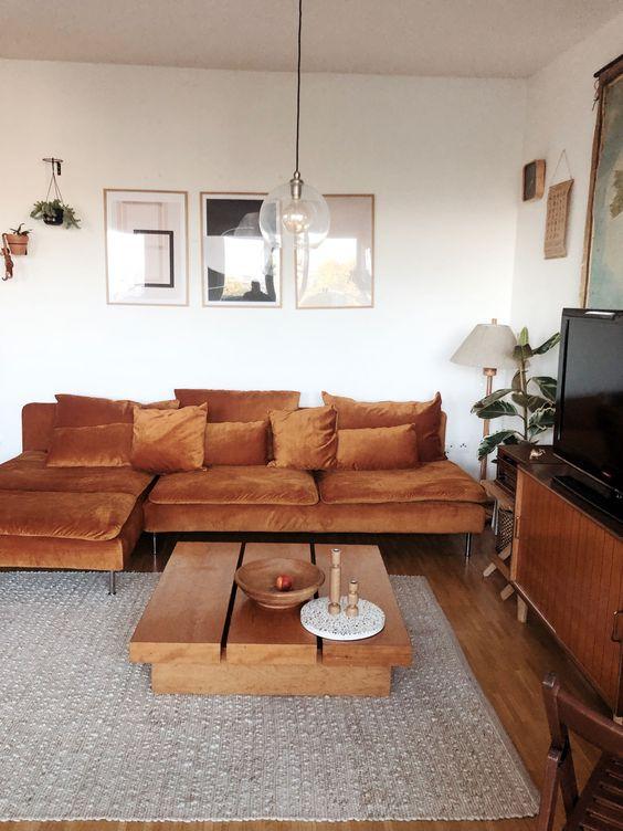 un raffinato soggiorno moderno con un'atmosfera anni '70, un divano IKEA color ruggine, mobili in legno, piante in vaso e opere d'arte
