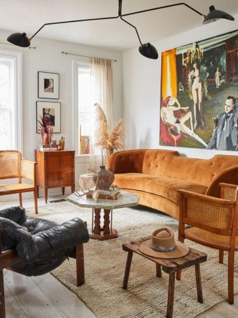 un accogliente soggiorno ispirato agli anni '70 con un divano color ruggine, mobili in rattan, legno e pelle, un lampadario nero e un'opera d'arte