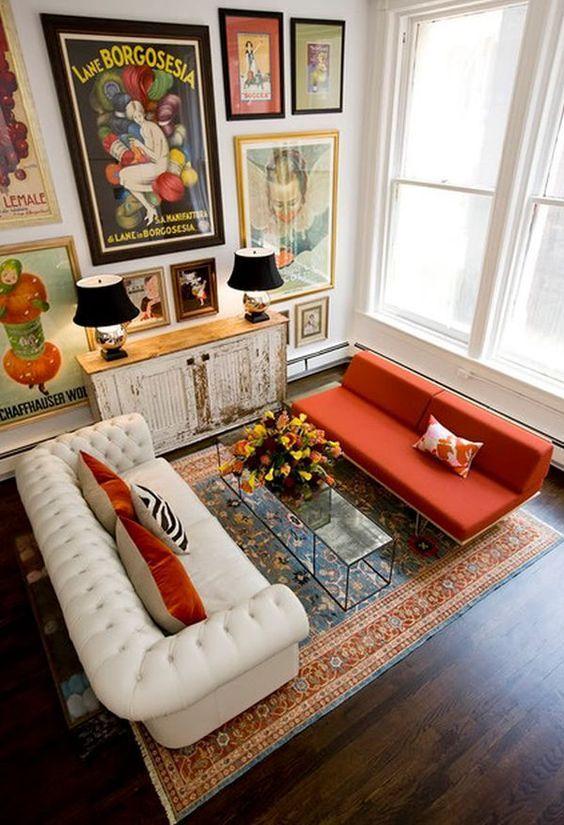 un soggiorno stravagante con una galleria a parete audace, un divano bianco trapuntato, un divano arancione, un tavolo di vetro e un armadio shabby chic
