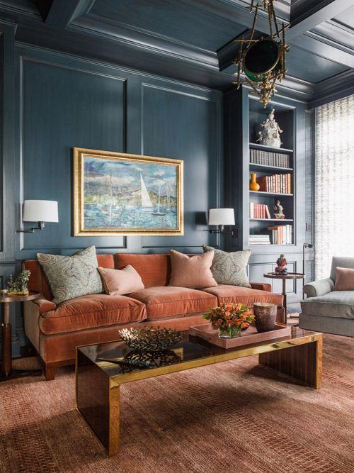 un soggiorno sofisticato con pareti blu scuro, un divano in velluto color ruggine, un tavolo basso lucido, mensole incorporate