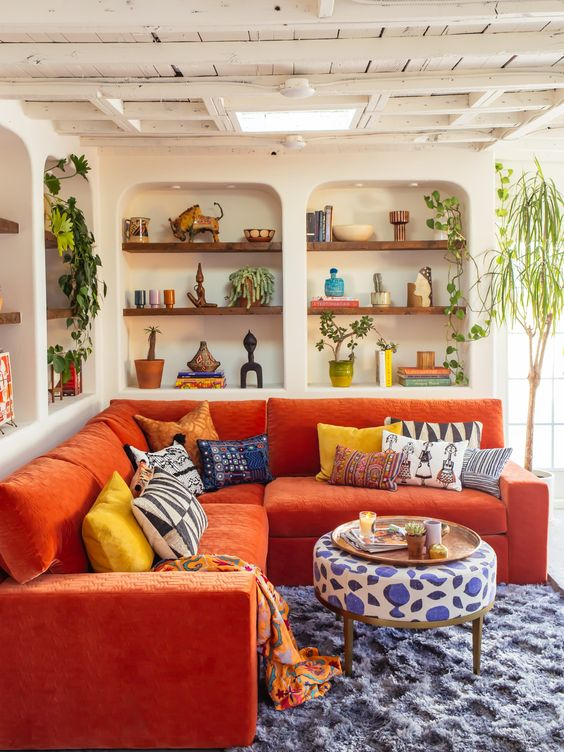 un vivace soggiorno con nicchie con mensole incorporate, un divano arancione, tessuti audaci e piante in vaso per un'atmosfera massimalista