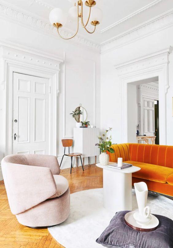 un soggiorno sofisticato con un divano arancione, una sedia rosa, un tavolo eccentrico e un cuscino più una brocca è uno spazio accattivante