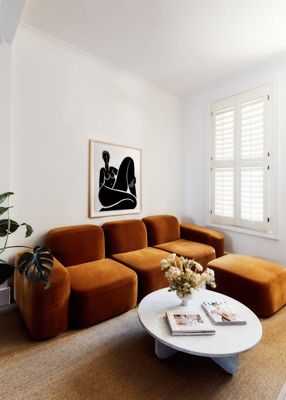 un soggiorno stravagante con un bizzarro divano color ruggine e un pouf, un tavolo rotondo e un'opera d'arte audace