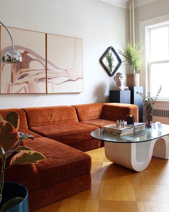 uno spazio stravagante con un sezionale color ruggine, un tavolo eccentrico, piante in vaso e un'adorabile opera d'arte è wow