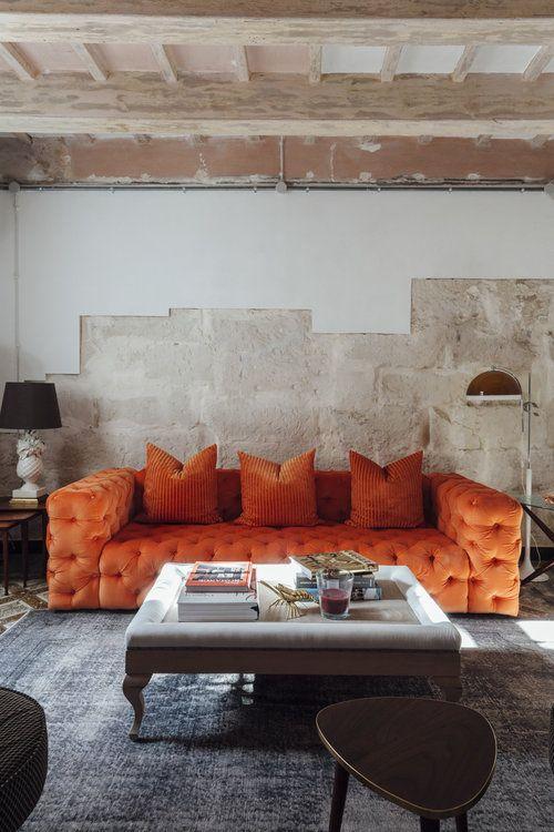un soggiorno industriale con pareti grezze, un raffinato divano trapuntato arancione, un tavolo basso in vetro e lampade da terra