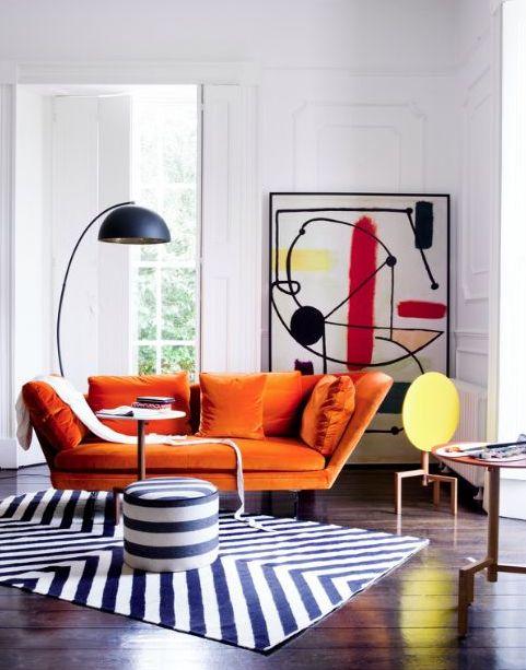 un soggiorno stravagante con un divanetto arancione, un'audace opera d'arte astratta, una lampada da terra e un tappeto geometrico e un pouf