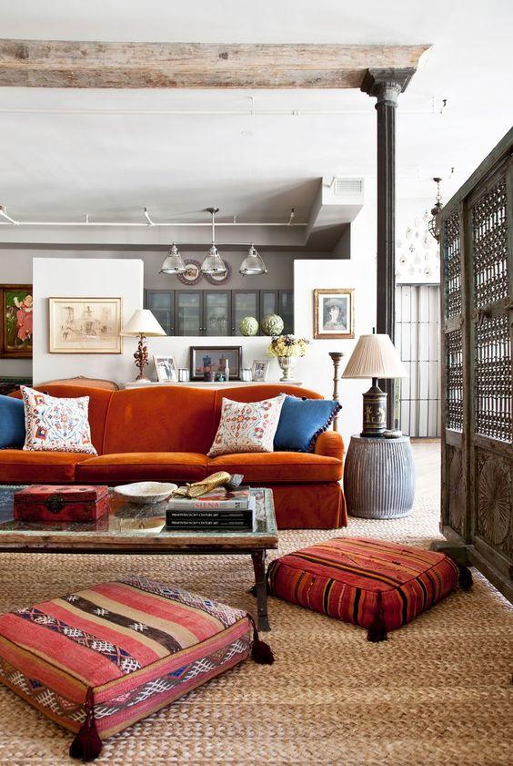 un soggiorno eclettico con un divano arancione bruciato, un tavolo basso e graziosi cuscini con nappe e una lampada da tavolo
