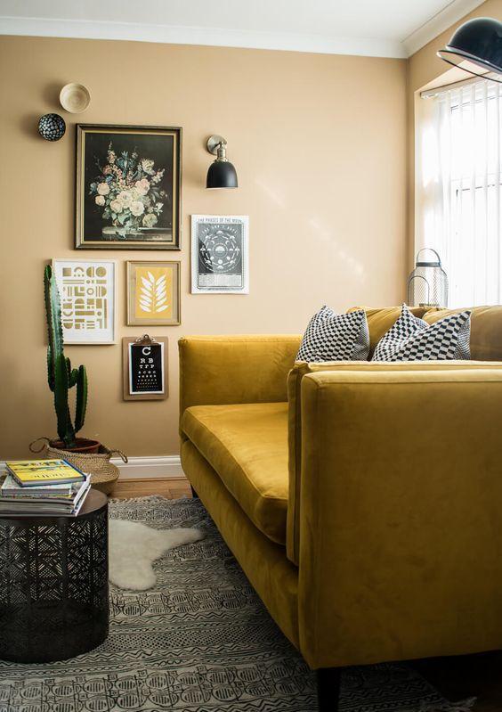 un angolo boho con pareti gialle, un divano senape, una galleria wlal e applique e tappeti a strati più un cactus in vaso
