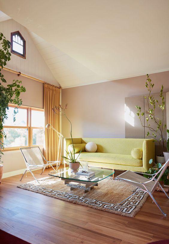 un audace soggiorno con pareti color talpa, un divano giallo, sedie moderne e un tavolo in vetro più piante in vaso è sorprendente