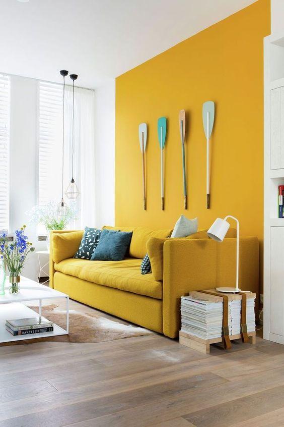 uno spazio audace con un muro color senape e un divano coordinato, remi per l'arredamento, un tavolo basso e riviste impilate è bizzarro