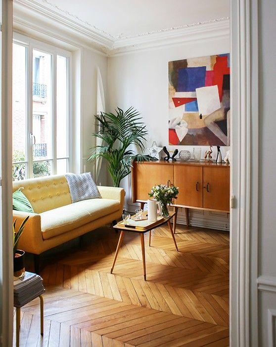 un luminoso soggiorno moderno con un divano giallo chiaro, un'opera d'arte colorata, mobili moderni della metà del secolo e vegetazione