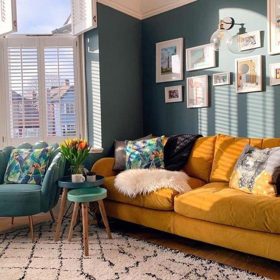 un soggiorno luminoso con pareti blu, un divano giallo e cuscini stampati, una sedia blu e tavoli rotondi è chic e accogliente