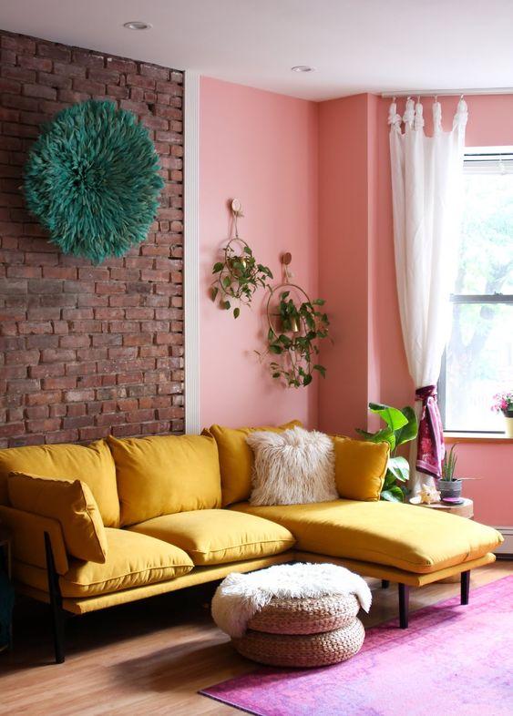 un soggiorno allegro con un muro di mattoni e rosa, un componibile giallo, pouf di iuta e vegetazione è sorprendente