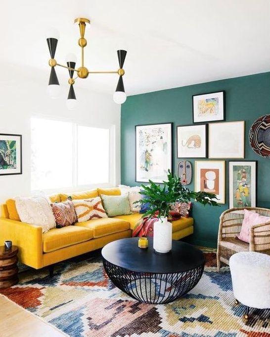 un luminoso soggiorno boho con una parete verde e una galleria a muro, un componibile giallo, un lampadario retrò e un tavolo rotondo nero