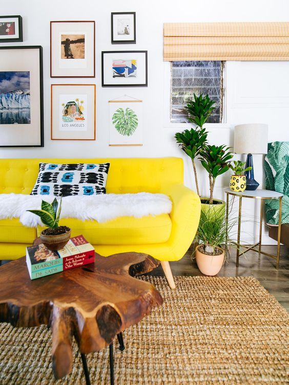 un soggiorno colorato con un divano giallo neon, una luminosa galleria wlal, piante in vaso e un tavolino da caffè in legno